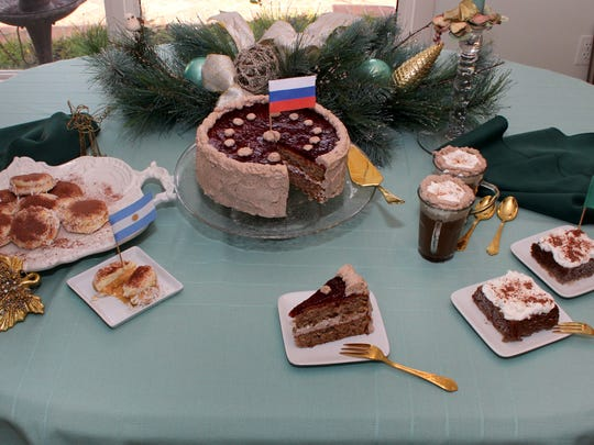A display of International Deserts are presented at the table of Carol Chargot. From left to right, Alfajores Sandwich Cookies, Russian Walnut Mocha Torte, Viennese Coffee, and Mexican Tres Leches.