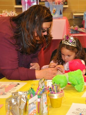 Tina Beakley helps her granddaughter Ysa McRae with a princess-themed craft at the Inspira Auxiliary Cumberland County's annual Princess Party in Vineland.