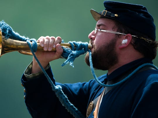 A Union re-enactor blows his trumpet signaling victory