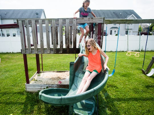 Emma Haines, 11, plays in a water sprinkler with her sister, Kayla, 11, at their home in Conewago Township.