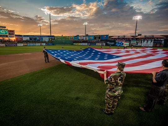 An American flag is unfurled for the playing of God Bless America and the Star-Spangled Banner before the Atlantic League All-Star Game on Wednesday at Clipper Magazine Stadium in Lancaster.