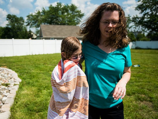 Emma Haines, 11, goes to her mother, Jennifer, after taking a swim in the family pool. Emma feels most comfortable in the pool. 'I always call her 'my little fish,'' Jennifer said. 'She's the one that stays in forever.'