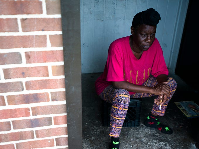 Sherry McGhee smokes a cigarette outside her apartment