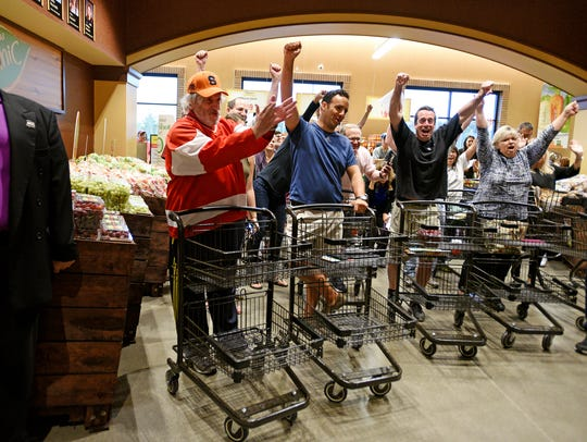 The first shoppers in line at the new Wegmans in Montvale give a cheer before shopping in the store on  Sept. 24.