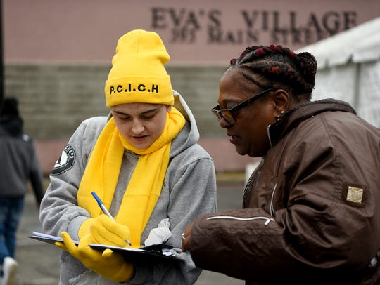 Americorps volunteer Danielle Lefebvre, left, performs a Point-in-Time Count homeless survey with a homeless woman outside of Eva's Village in Paterson on Wednesday.