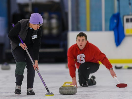 Laura Thompson (left) follows her teams stone while waiting instruction from the team skip on Tuesday night at The Pavilion.