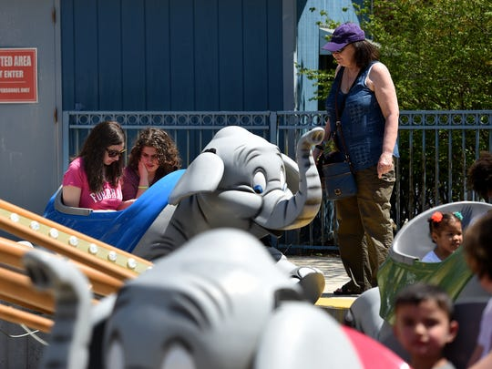 Barbara Strate watches to make sure her daughter, Sarah Strate 22, far left, and family friend, Gina Krieger 21 of Washington Township, are properly buckled into the ride, both girls are on the autism spectrum. The first ever Autism Day was held at Six Flags Great Adventure in Jackson on Thursday, May 3, 2018. The park was transformed into a sensory-friendly environment, including adjusted lights and music and decompression areas, for individuals on the autism spectrum, their friends, and families.