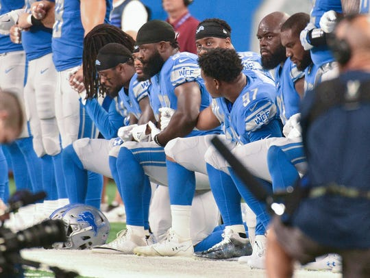 Detroit Lions players kneel.