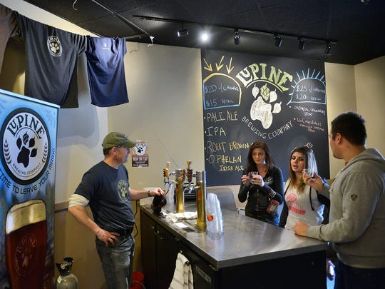 Lupine Brewing Co. President James Anderle, left, fills a growler as Becca Crowe, left center, Loretta Crowe and Justin Strzyzewski, all of St. Cloud, sample some of the six varieties of beer Lupine had on stock Thursday.