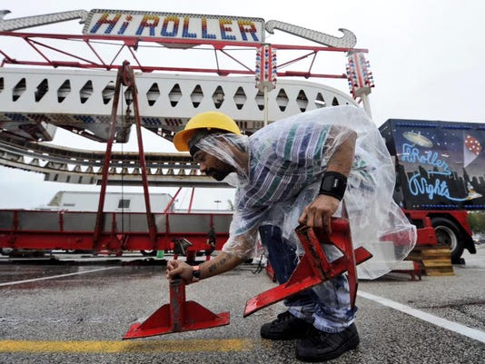 A worker sports a poncho while putting rides together for the York Fair.