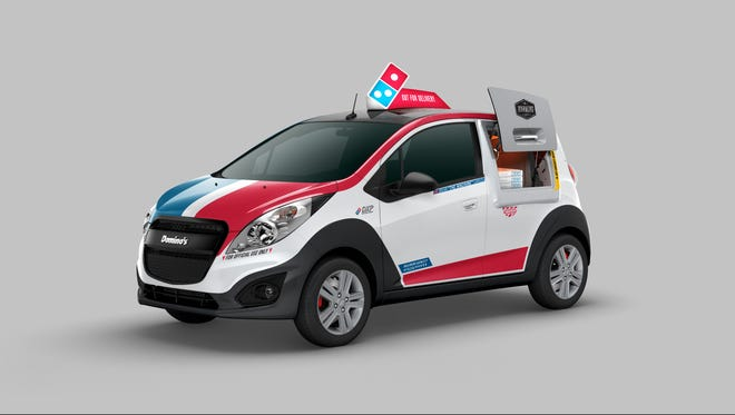 The pizza delivery giant headquartered in Ann Arbor is planning to convert 100 Chevy Sparks subcompacts into red, white and blue pizza delivery cars with a warming oven accessible through an exterior hatch next to the driver's door. Oct. 21, 2015