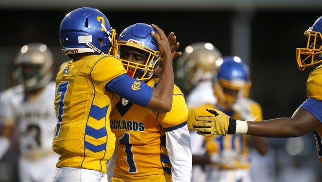 Rickards quarterback D.J. Phillips, left, hugs teammate Kalen Riles after he caught a touchdown pass during their game against Lincoln.