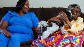 Compassus nurse assistant Shelia Shelton chats with hospice patient Etta Howard while she plays with a dog.