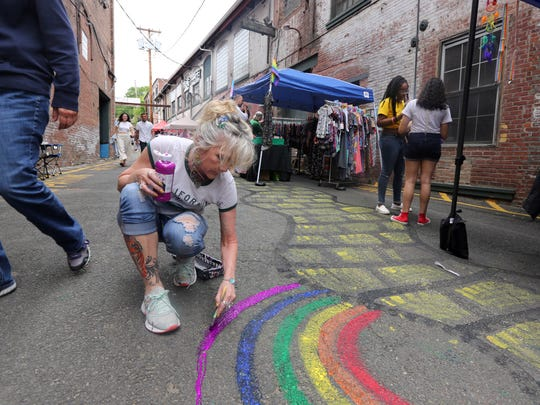 "Eve Fernandez of Airmont paints rainbows on the sidewalk during Rockland's 20th Pride Sunday at the Garner Historic District in Garnerville June 10, 2018. Hundreds or people attended the event, which was sponsored by the Rockland County Pride Center. The day included live music, kid activities, food trucks, ""drag queen storytelling"" and more."