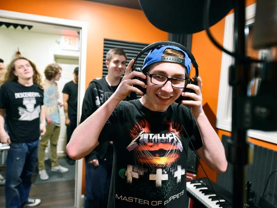 Hanover sophomore Nash Miller tries on headphones in AK Beatz's recording booth during a one-day music production class at Studio 117 in York. The class was part of the York County Alliance's career exploration program.