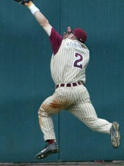 Seminole center fielder Shane Robinson (2) makes a spectacular sixth-inning-ending catch before slamming into the wall against UCF in their first NCAA Regional baseball game Sunday. The catch ended the inning and prevented more runs from scoring, but the Seminoles' lost 7-5, and a second game was forced.