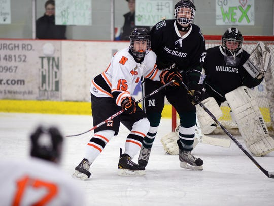 Northville's Nick Strom (15) and Novi's Ryan Turner (12) jockey for position in front of Wildcats netminder Josh Richardson as the Mustangs' Kevin O'Connell unloads a shot.