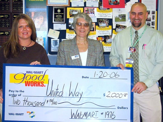 Tina Jones, left, and Matt Huyck, right, present a $2,000 donation from Walmart to Cathy Gschwind, United Way Chemung County community campaign director in this file photo.