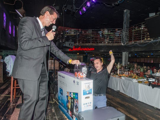 Montgomery Advertiser president Michael Galvin, left, presents a new TV during a prize drawing at the Montgomery Advertiser's 2018 Reader's Choice Best of the Best Awards on Thursday, July 26, 2018, at B.B. King's Blues Club in Wind Creek Montgomery.