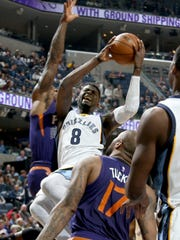 Memphis Grizzlies James Ennis, center, shoots against the defense of Phoenix Suns Eric Bledsoe, left, and P.J. Tucker, right, at FedExForum.