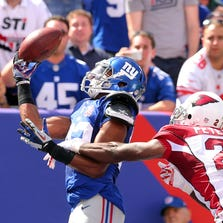 Sep 14, 2014: New York Giants wide wreceiver Rueben Randle (82) catches a touchdown pass in front of Arizona Cardinals corner back Patrick Peterson (21) during the second quarter at MetLife Stadium.
