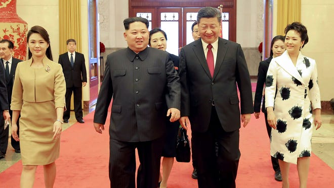 China's President Xi Jinping and his wife Peng Liyuan, North Korean leader Kim Jong Un and his wife Ri Sol Ju walking in the Great Hall of the People in Beijing,  March 26, 2018. Kim Jong Un was treated to a lavish welcome by Chinese President Xi Jinping during a secretive trip to Beijing as both sides seek to repair frayed ties ahead of landmark summits with Seoul and Washington.