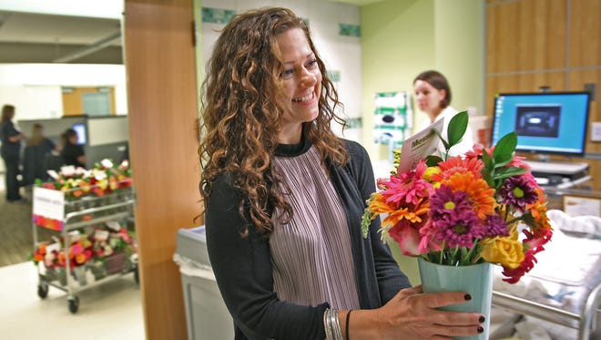 Amy Toosley, with FTD, delivers flowers from Random Acts of Flowers to Eskenazi Hospital patients, Thursday, Oct. 13, 2016. The Knoxville, Tenn.-based nonprofit debuts its fifth chapter, this one in Indianapolis. Started about a decade ago by a film and television producer who was injured in an accident, Random Acts of Flowers accepts donations of flowers from florists, distributors, event planners and individuals, then repurposes them for people in nursing homes and hospitals whose own rooms are floral-free.