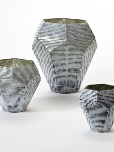 This photo provided by Wayfair.com shows Stria vases. The Stria vase collection?s hallmark is a graphic faceted shape.