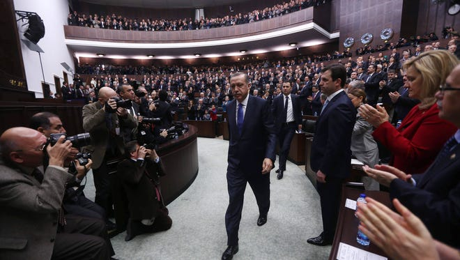 Turkey's Prime Minister Recep Tayyip Erdogan walks on his way to address members of the parliament from his ruling AK Party during a meeting at the Turkish parliament in Ankara on January 28, 2014.