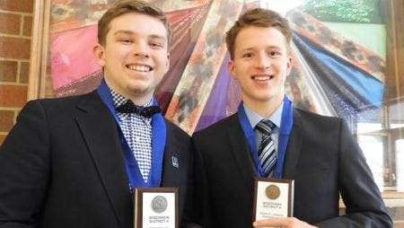Connor Duffy, left, and Brandon Stillman, students at Gibraltar High School, pose holding the awards they won in a DECA competition Jan. 13, 2018.