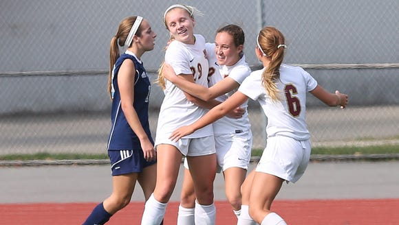 Arlington's Meggie Buttinger (2) is greeted by teammates