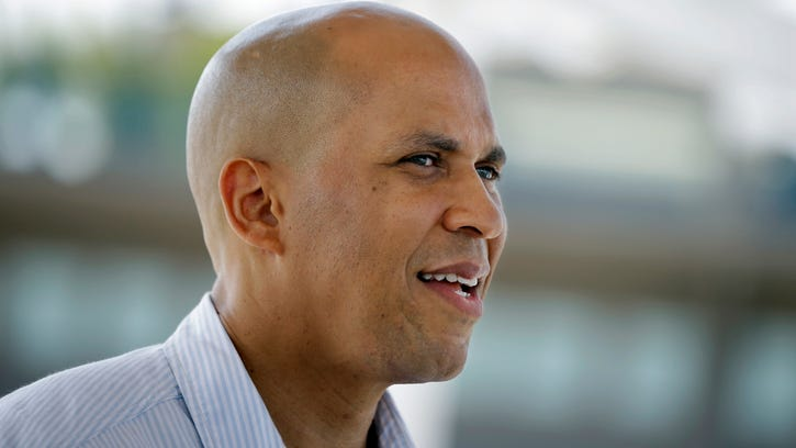 In this Sunday, Aug. 31, 2014 photograph, Sen. Cory Booker greets people as he walks along the boardwalk in Long Branch, N.J. Booker will face Republican Jeff Bell in November. New Jersey has not elected a Republican to the U.S. Senate since 1972, but conservatives think they have a chance with Bell, a little-known candidate taking on the well-funded Booker. (AP Photo/Mel Evans)   ORG XMIT: OTKME101