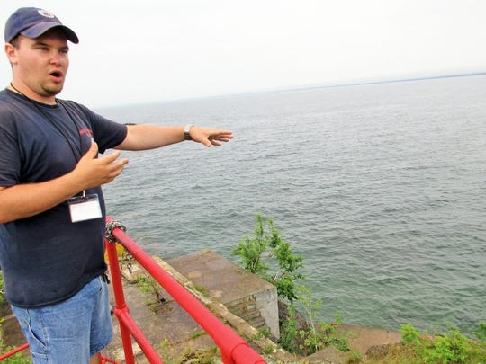 ADVANCE FOR SUNDAY, JULY 24 AND THEREAFTER - In this July 7, 2016 photo, Marquette Maritime Museum seasonal manager Ryan Dubay talks about the remnants of a building at the end of the Harbor Lighthouse catwalk in Marquette, Mich. The museum has chronicled and celebrated life on the Great Lakes for well over a century. (Lisa Bowers/The Mining Journal via AP)