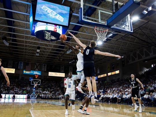 Florida Gulf Coast University guard Brandon Goodwin (0) drives to the net against the University of North Florida defense during their matchup at Alico Arena on Monday. The Eagles beat the Ospreys 103-70.