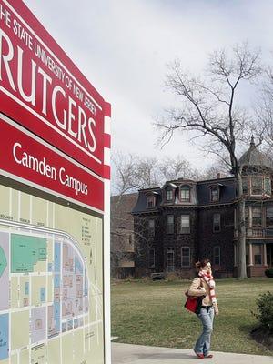 File: A student walks by a Rutgers University information board. (AP Photo/ Jose F. Moreno)