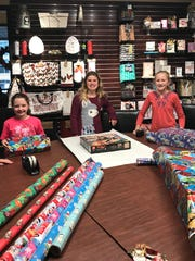 Isabella Besco, center decided to offer gift wrapping for donations to the Penny Drive. She and her cousin Maddy Estok, left, and friend and fellow Battle Ground Academy student Elizabeth Bowman raised $208 for Second Harvest.
