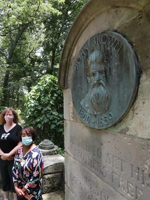 """Summit County Historical Society CEO and President Leianne Neff Heppner, left, and Summit County Historical Society board member GinaKaye Maddox stand beside the John Brown monument Thursday July 2, 2020, in Akron. The inscription beneath the medallion reads, """"He died to set his brothers free."""""""