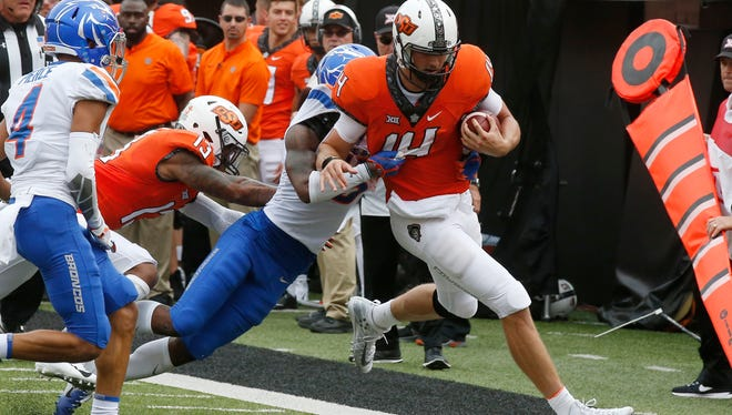 Oklahoma State quarterback Taylor Cornelius is pushed out of bounds by Boise State cornerback Jalen Walker.