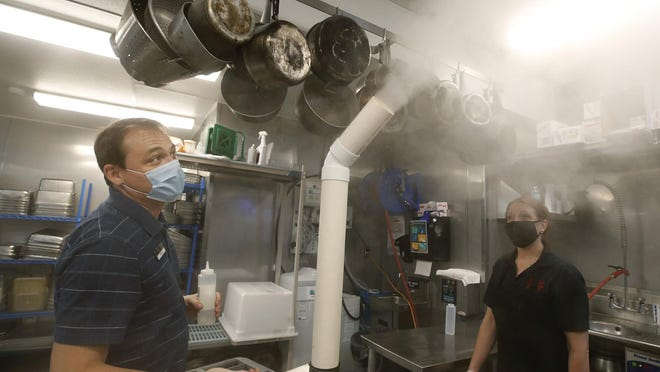 Norwood's manager Travis Walters uses the ultrasonic nebulizer to sanitize at Norwood's Eatery and Treehouse Bar in New Smyrna Beach, Sunday, July 5, 2020. The machine produces an effective disinfectant that's non-irritating on skin and doesn't harm the environment.