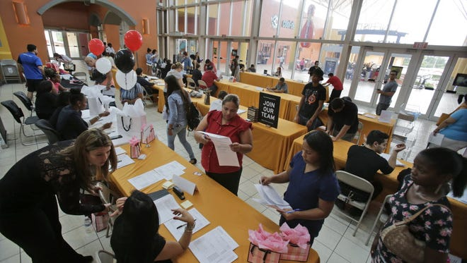 People attend a job fair at Dolphin Mall in Miami. The federal government issues its October jobs report on Dec. 4.