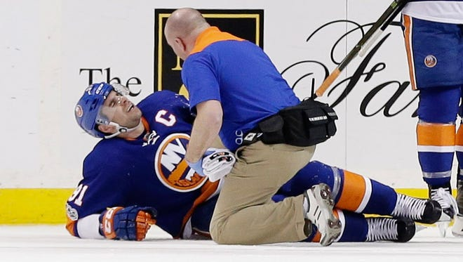 A trainer checks on New York Islanders forward John Tavares after he was injured during the third period against the New Jersey Devils on Friday.