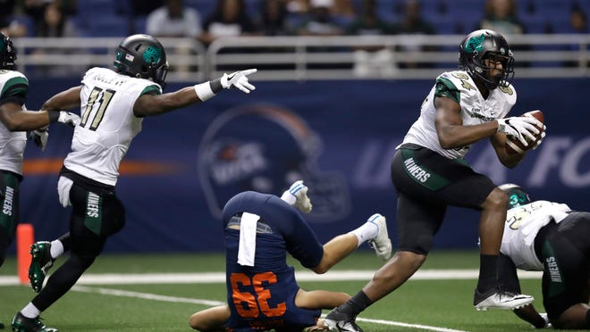 Charlotte's Juwan Foggie (84) runs past UTSA punter Yannis Routsas (39) as he scores on a bobbled punt attempt during the second half of an NCAA college football game, Saturday, Nov. 26, 2016, in San Antonio. (AP Photo/Eric Gay)