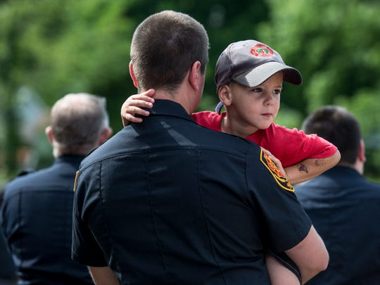 Firefighter Tyler Slyford holds his son, James, 3, during a groundbreaking ceremony for the new Kimball Township fire station Thursday, July 28, 2016 at Station 1 on Allen Road in Kimball Township.