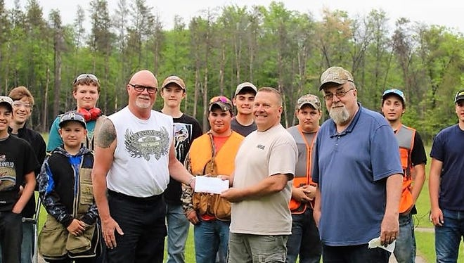Glenn Sowle, left, president of the WGAS Association in Oconto, recently presented a $1,000 donation to Oconto Youth Trap team, to Todd Bronikowski, center, the team's adviser, and Rudy Kapla, who assists with the program. Behind them are several members of the team.