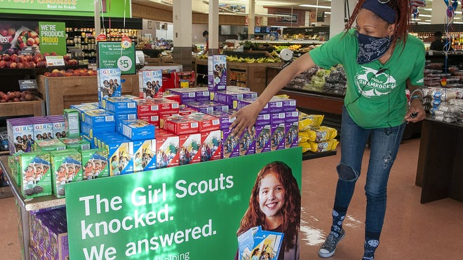 Price Chopper employee Kendra Shine straightens the display of Girl Scout cookies for sale inside the grocery store on Park Avenue Friday.