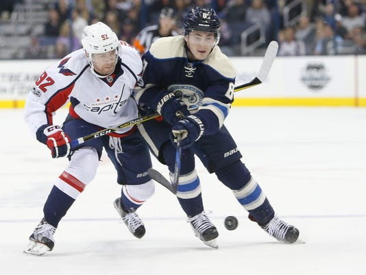 Columbus Blue Jackets' Zach Werenski, right, carries the puck across the blue line as Washington Capitals' Evgeny Kuznetsov, of Russia, defends during the second period of an NHL hockey game Sunday, April 2, 2017, in Columbus, Ohio. (AP Photo/Jay LaPrete)