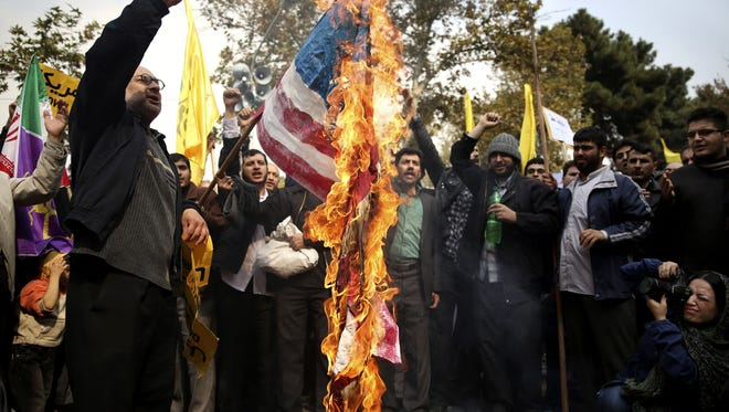 Iranian protesters burn an American flag as tens of thousands packed the streets Monday outside the former U.S. Embassy in Tehran in the biggest anti-American rally in years.