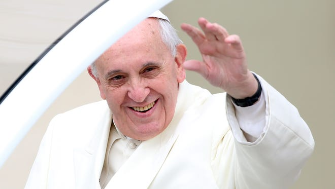 Pope Francis waves to the crowds as he arrives in St. Peter's Square for his weekly audience on Jan. 22, 2014, in Vatican City.