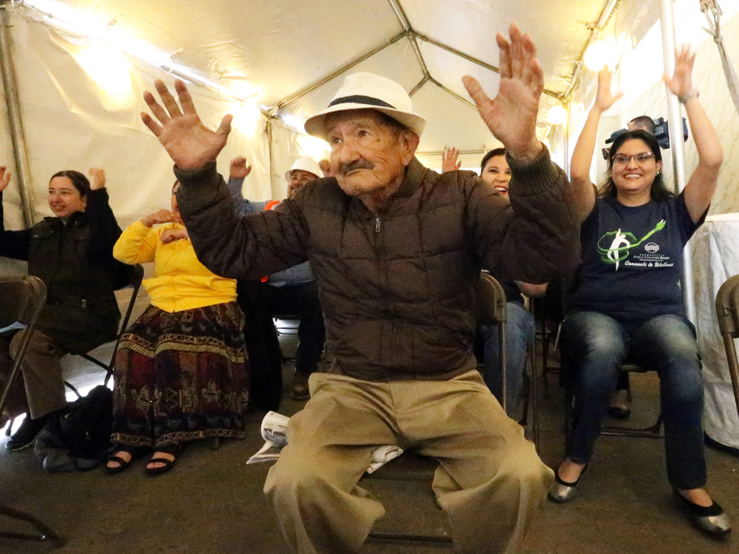 Ruperto Pedraza, 82, takes part in chair aerobics in a tent outside an H.E.B. grocery store in Brownsville, TX. The store chain provides free periodic talks on healthy eating, health screenings and exercises.