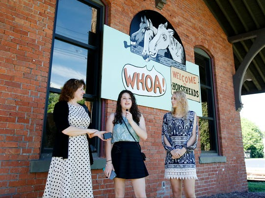 From left, Horseheads High School art teacher Cynthia Cratsley-Harrington, and students Amelia O'Shell and Cassandra Cavanaugh talk about the process in recreating the iconic city welcome signs originally designed by cartoonist Eugene Zimmerman.